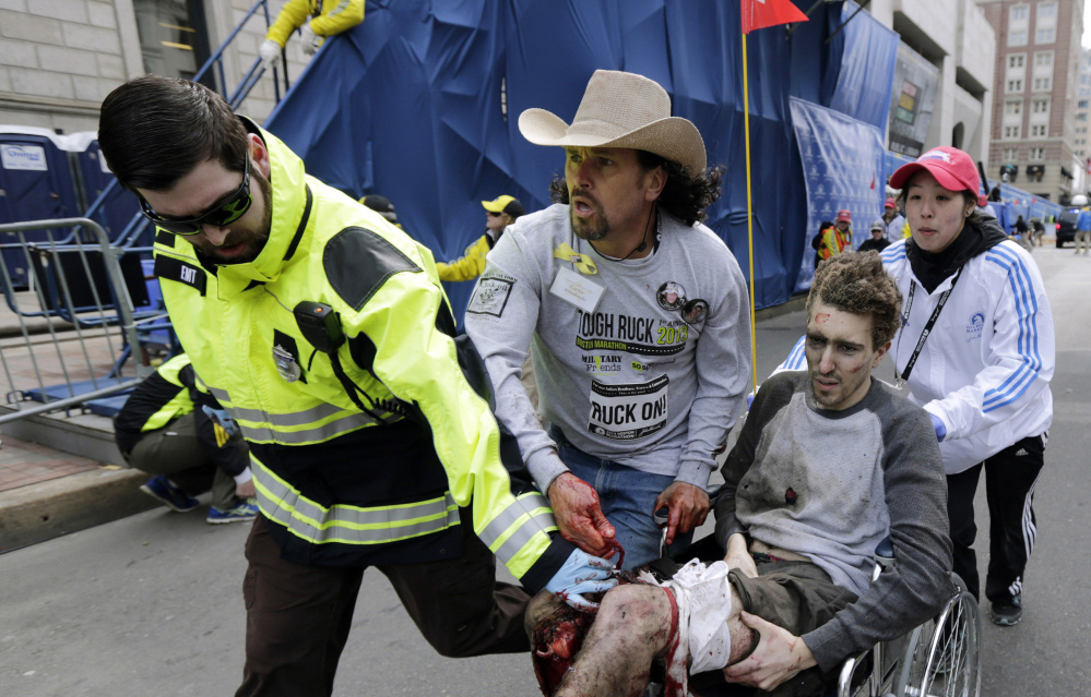 Boston EMT Paul Mitchell, left, bystander Carlos Arredondo, in cowboy hat, and Boston University student Devin Wang push Jeff Bauman in a wheelchair after he was injured in one of two bomb blasts near the finish line of the Boston Marathon in April 2013. The first feature-length documentary film highlighting historical moments of the nation's oldest marathon is in the works, tentatively set to premiere in April 2017 in conjunction with the 121st running of the race.