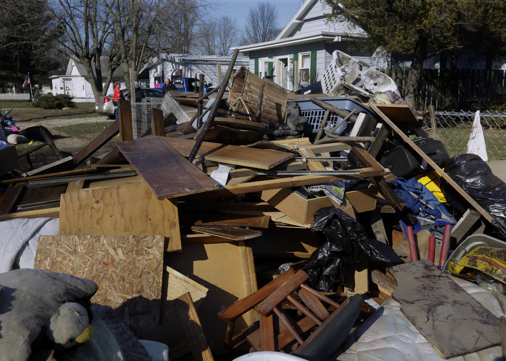 Central Illinois residents pile ruined furniture, appliances and clothes along the street for disposal crews to pick up Sunday after last week's flooding from the south fork of the Sangamon River in Kincaid, Ill.