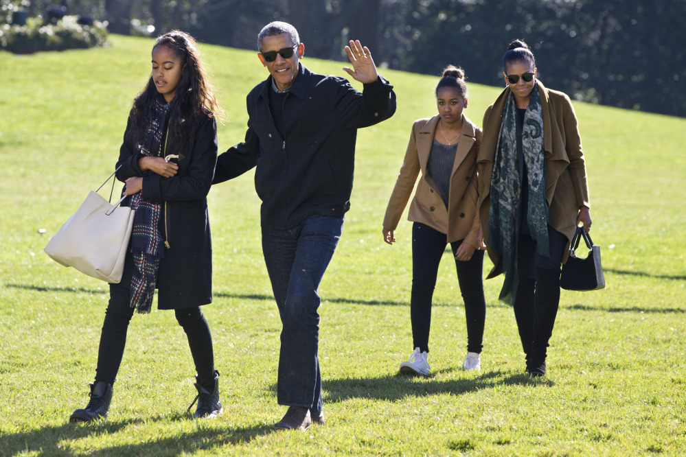 President Barack Obama waves as he walks across the South Lawn with daughter Malia, left, followed by Sasha Obama and first lady Michelle Obama, on their return to the White House, in Washington on Sunday after a family vacation in Hawaii.