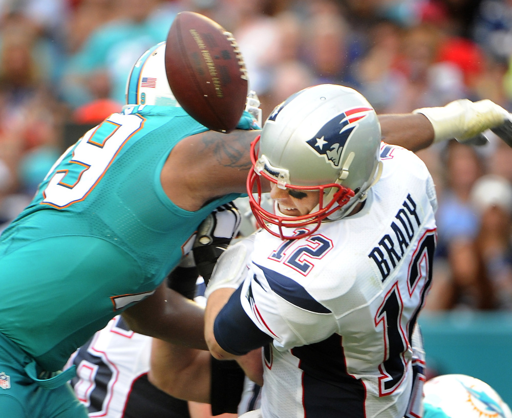 Patriots quarterback Tom Brady has the ball stripped by Miami's Derrick Shelby during a bruising 20-10 loss to the Dolphins Sunday that denied them home-field advantage.
