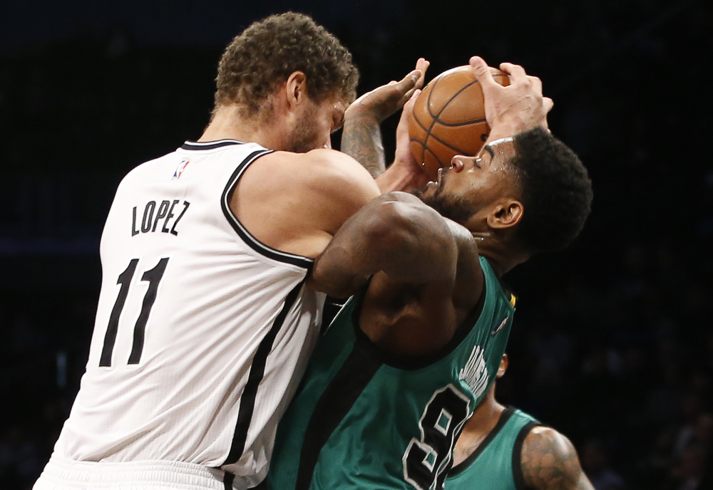 Nets center Brook Lopez and Celtics forward Amir Johnson get tangled up under the Nets' basket in the first half of the Celtics' 103-94 win.