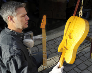 Richard Roth inspects the finish on one of his vintage guitars he is rebuilding. Gordon Chibroski/Staff Photographer