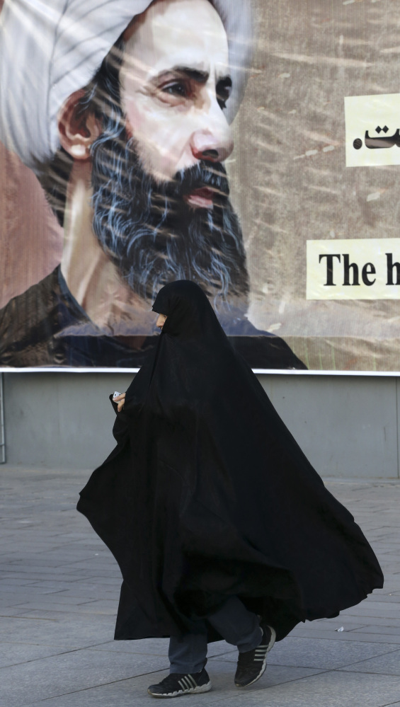 An Iranian woman walks past a portrait of Sheikh Nimr al-Nimr, who was executed by Saudi Arabia last week)