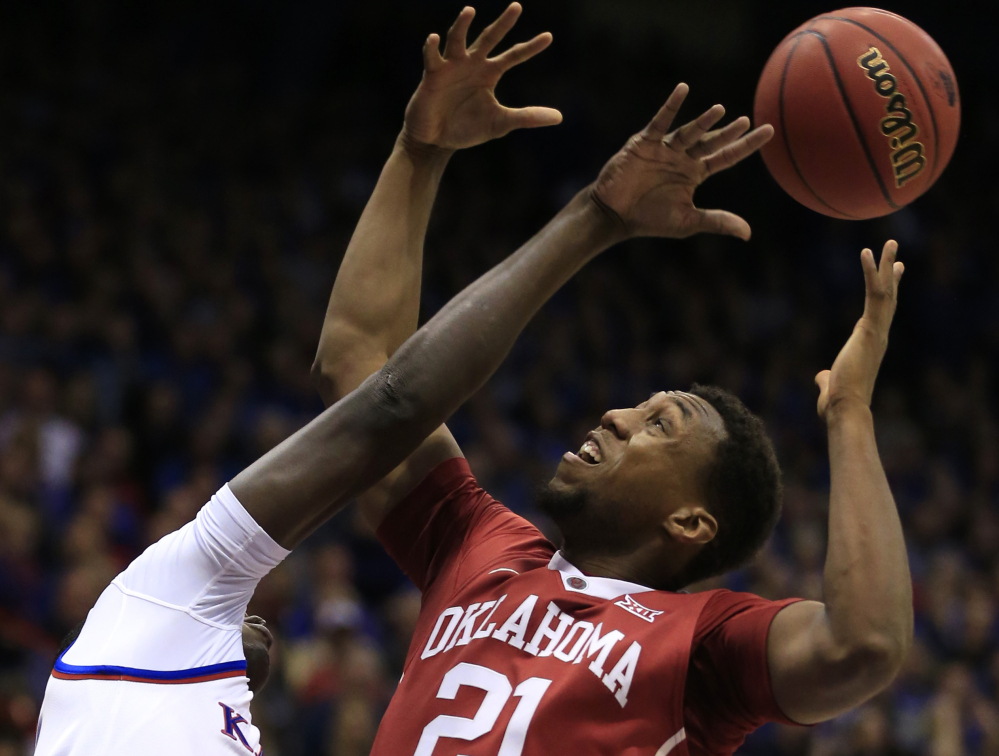 Kansas forward Cheick Diallo, left, knocks the ball away from Oklahoma forward Dante Buford, right, during the first half of an NCAA college basketball game in Lawrence, Kan., Monday, Jan. 4, 2016. (AP Photo/Orlin Wagner)