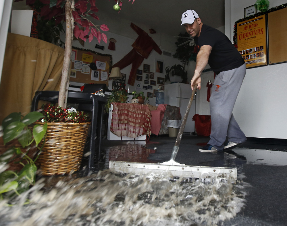 A building owner sweeps out following heavy rain in Sacramento, Calif., on Tuesday. The current El Niño has tied with the 1997-1998 one as the strongest on record.