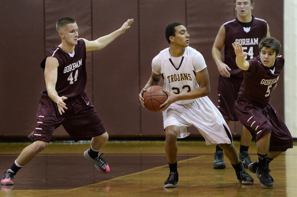 Thornton Academy's Corey Hart, center, looks to pass while being defended by, from left, Gorham's Billy Ruby, Logan Drouin and Cody Elliott on Tuesday in Saco.