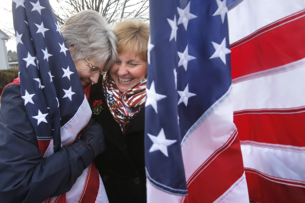 Freeport flag lady Elaine Greene, left, gets a hug from Maine first lady Ann LePage Dec. 22. A reader says James Roux III, who objects to the group's pro-military message linked to the Sept. 11 attacks, is often portrayed unfairly.