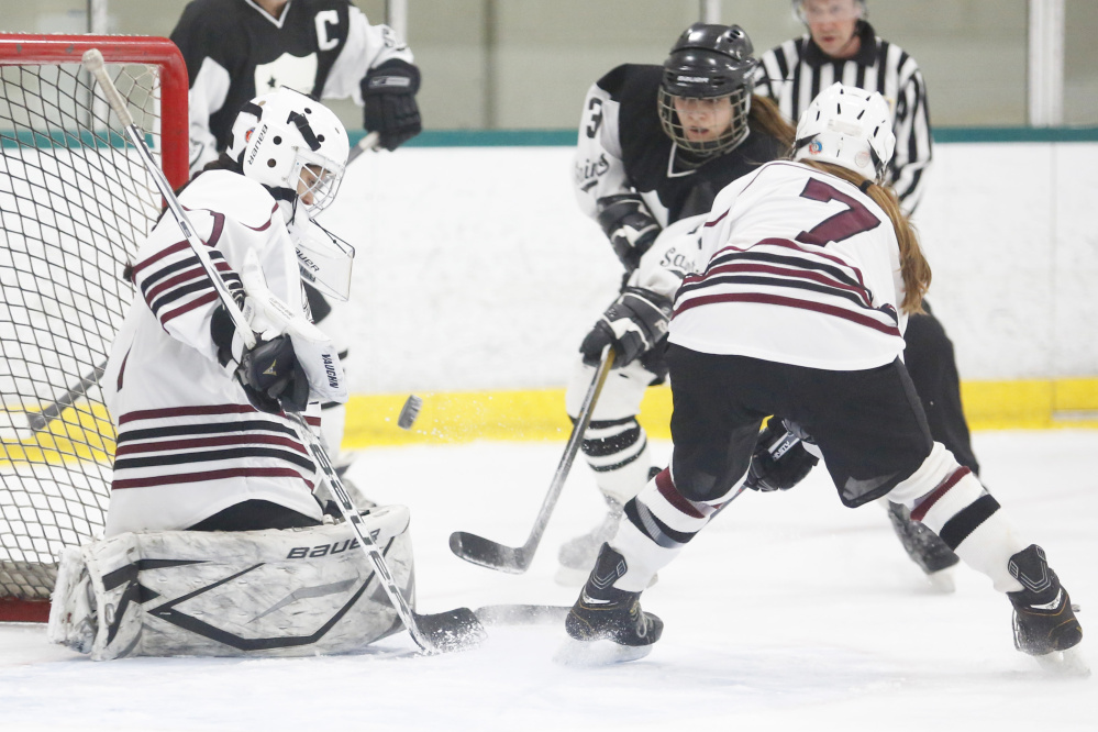 Greely's Nica Todd makes a save on Lexie Kesaris of St. Dom's in Wednesday night's game at Falmouth. Todd gets some help in front of the net from Bridget Roberts, who scored the winning goal in the third period.