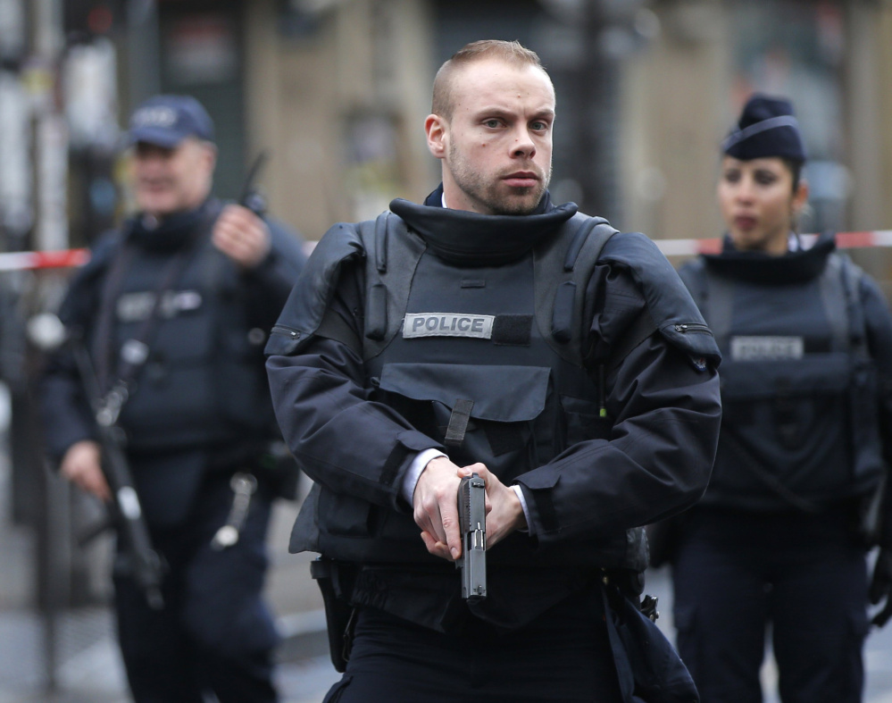 Paris police secure the scene of a fatal shooting at a police station Thursday. French officials say a man armed with a knife was shot to death by officers in northern Paris.