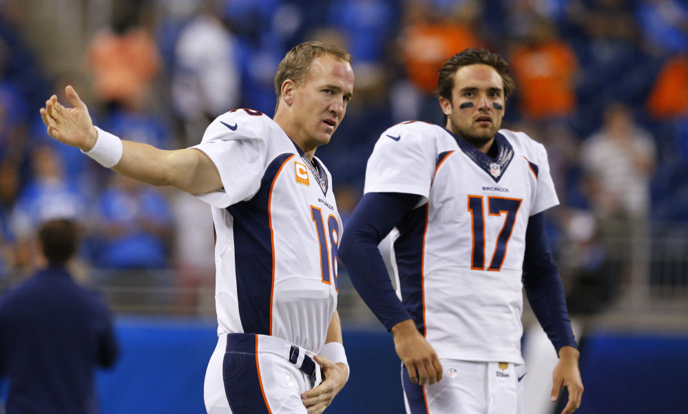 Denver Broncos quarterbacks Peyton Manning and Brock Osweiler get ready for a game against the Detroit Lions in Detroit on Sept. 27.