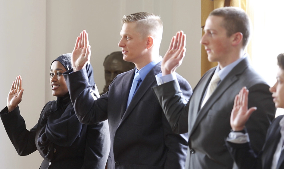 Zahra Abu, left, is sworn in along with Darrel Gibson, David Moore and Concetta Puleo during Friday's ceremony at Portland City Hall. Abu is Portland's first Somali officer.