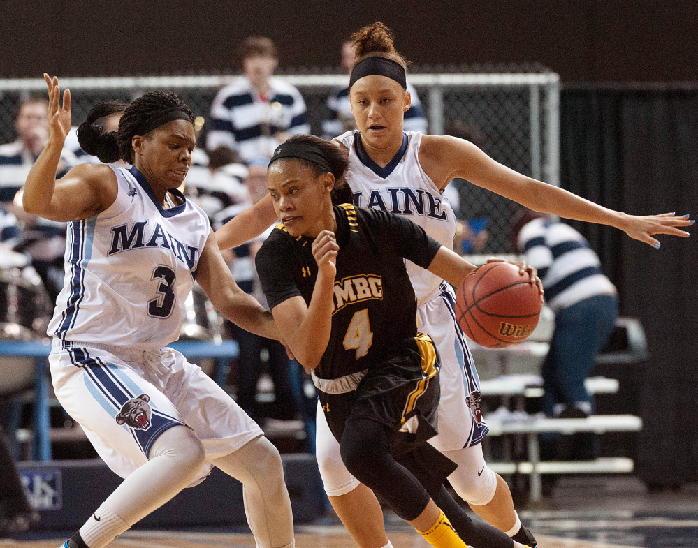UMaine's Bella Swan, right, and Chantel Charles put the brakes on UMBC guard Taylor McCarly in the second half of their America East game at the Cross Insurance Center in Bangor on Saturday. Michael C. York/Special to the Telegram