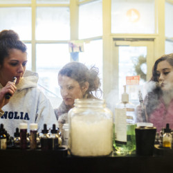 Emily Healy, left, Kristina Samar, center, and Justice Degregorio try different flavors of vape liquid at Old Port Vape in Portland. Maine is potentially looking to tax vape products much like tobacco, although many people use vaping to quit smoking.
