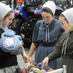 Lilia, left, Cassia and Moriah Higgins inspect yarn on display on the first day of the Agricultural Trades Show at the Augusta Civic Center.