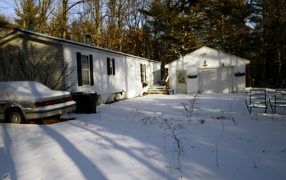A vehicle with no license plates sits next to the mobile home of Lucie McNulty on Atkins Lane, one of only a handful of residences on the dead-end street in Wells.