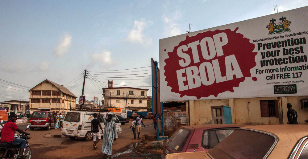 """People pass a banner reading """"STOP EBOLA,"""" forming part of Sierra Leone's Ebola-free campaign in the city of  Freetown, Sierra Leone, on Friday."""