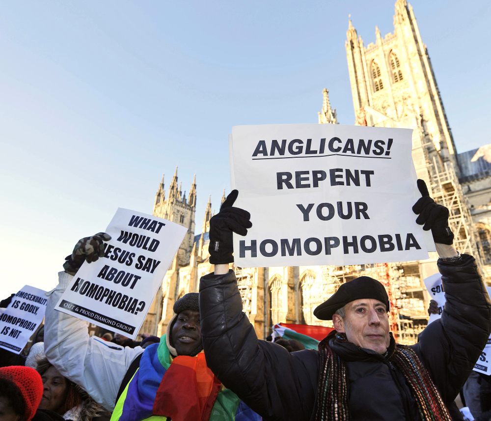Human rights campaigners in Canterbury, England, demonstrate on Friday against the decision by Anglicans to punish pro-gay marriage Episcopal churches in America.