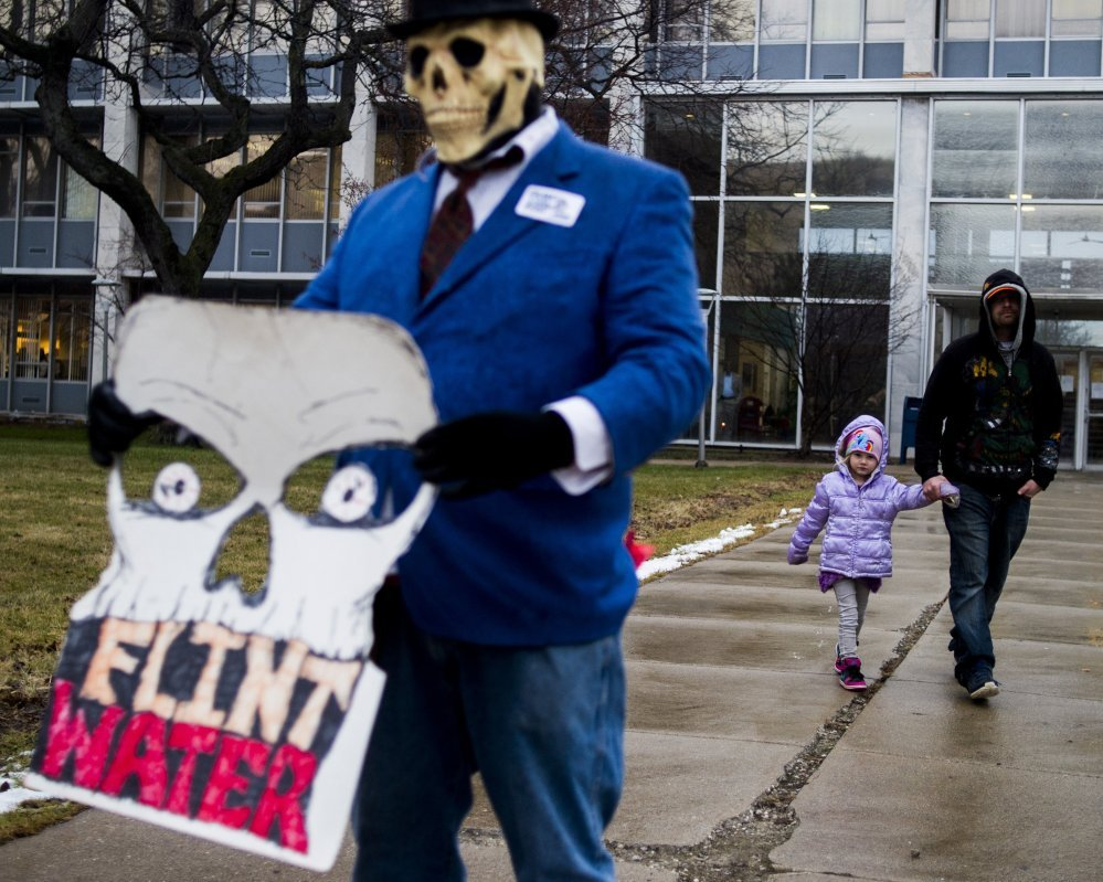 Flint resident Mike Hickey holds the hand of his daughter Natielee, 4, as they walk past activists protesting against Michigan Gov. Rick Snyder's handling of the water crisis on Jan. 8 in Flint. Mich. The Associated Press