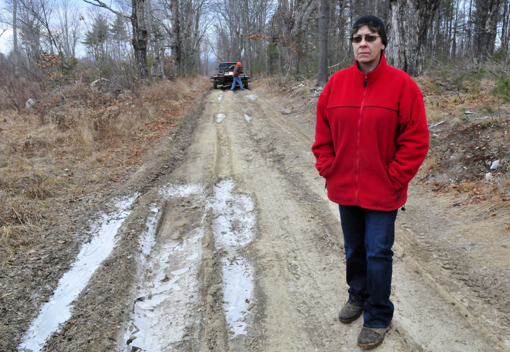 Fayelyne Genness stands in the middle of the unmaintained Brown Road extension that leads to her home in Mercer. Behind her is property owner and First Selectman Vern Worthen, who Genness says is trying to block her access. Morning Sentinel photos