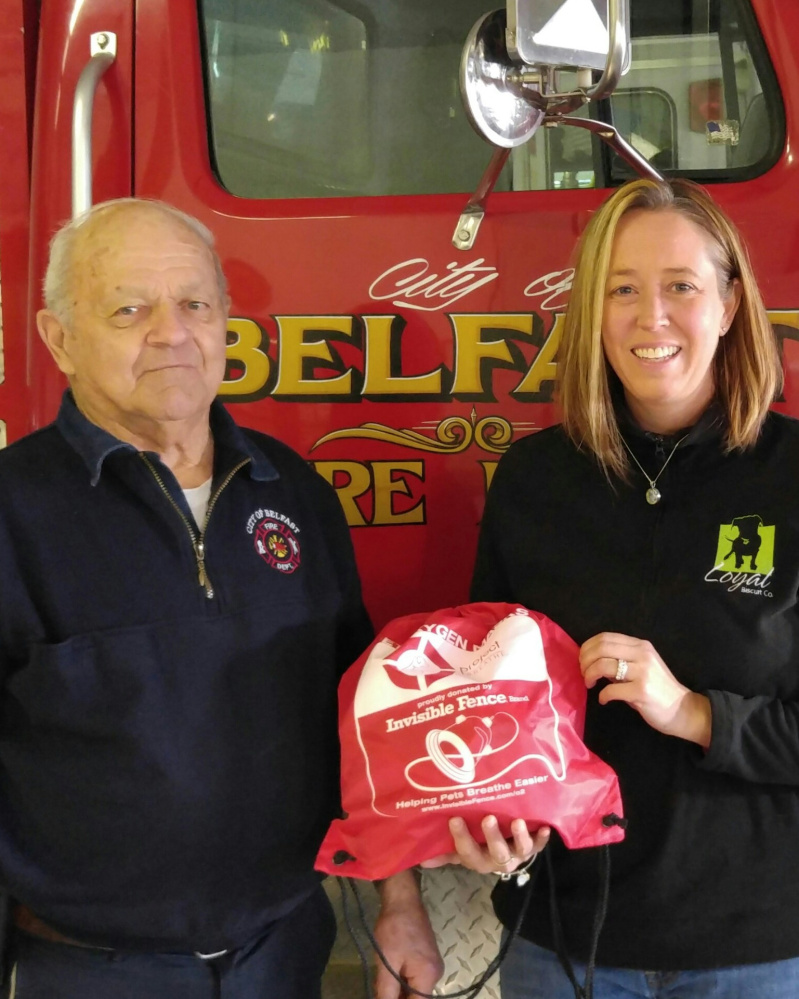 Heidi V. Neal, owner of The Loyal Biscuit Co., presents Belfast Fire Department Chief James Richards with a pet oxygen mask. Funds were raised through the Loyal Biscuit's partnership with the Maine POM Project.