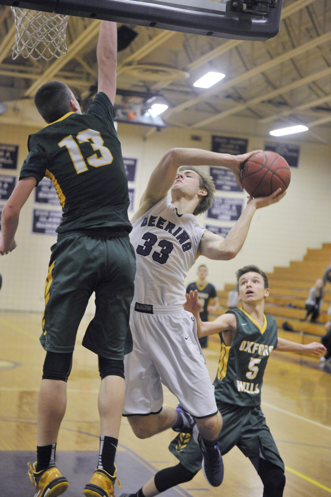 PORTLAND, ME - JANUARY 18: Deering vs. Oxford Hills boys basketball game. Deering's #33, Orey Dutton, finds his drive to the basket blocked off by Oxford Hill's #13, Matt Fleming.
