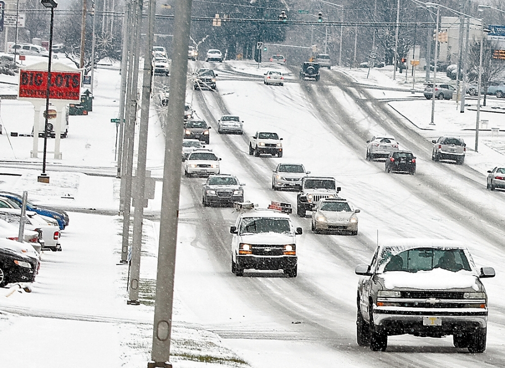 As snow falls, traffic moves slowly along slippery roads in Alcoa, Tenn., Wednesday. The South and East braced for blizzard conditions with the potential for significant snowfall by week's end.