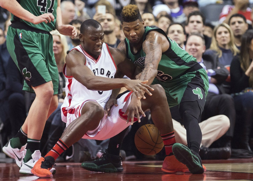 Toronto center Bismack Biyombo goes for a loose ball against Celtics guard Marcus Smart in the first half.