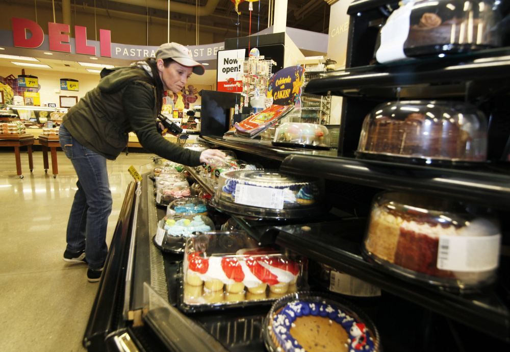 Shannon LeBlanc, bakery service leader at Hannaford in Westbrook, checks the dates on cakes and other bakery items for food pantry donations. Jill Brady/Staff Photographer