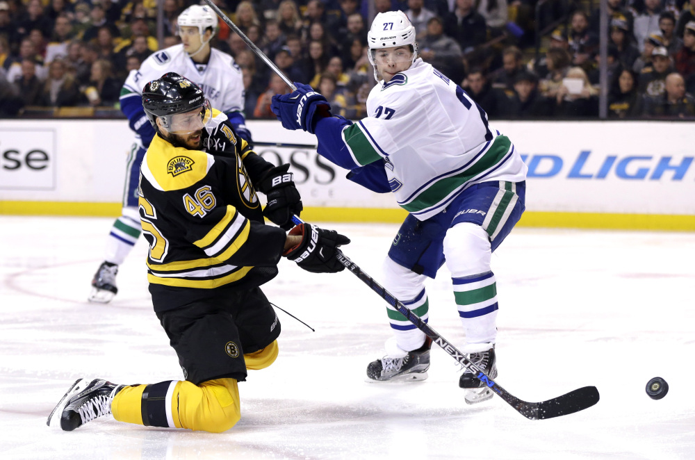 Bruins center David Krejci goes down on a knee in an attempt to control the puck against Vancouver defenseman Ben Hutton in the second period Thursday night in Boston.