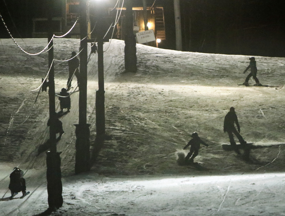 Skiers and snowboarders make their way down Powderhouse Hill while others use the rope tow to get back to the top for another run.