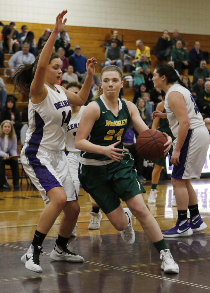 McAuley's Emily Weisser, center, drives to the basket while being guarded by Deering's Delaney Donovan, left, during the Lions' 52-43 win Friday at Deering. Joel Page/Staff Photographer