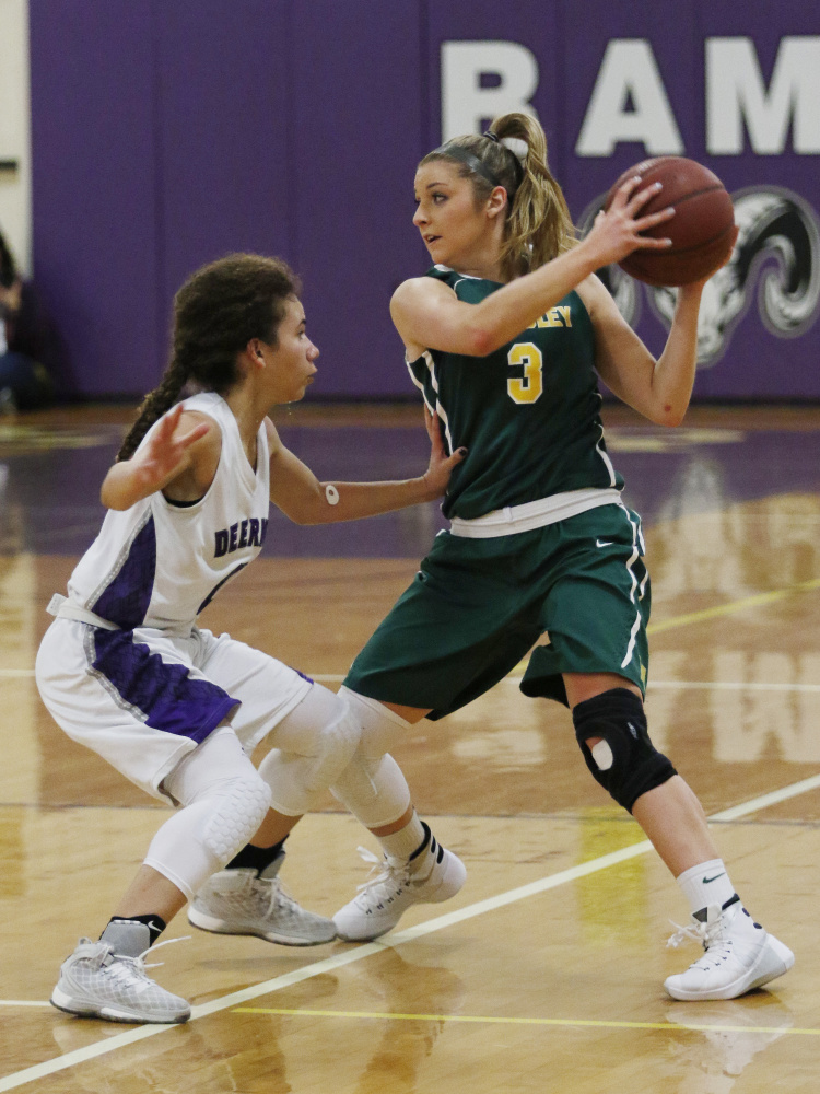 McAuley's Sarah Clement, right, looks for an open teammate while being guarded by Deering's Abby Ramirez, left, during the first half Friday in Portland. Joel Page/Staff Photgrapher