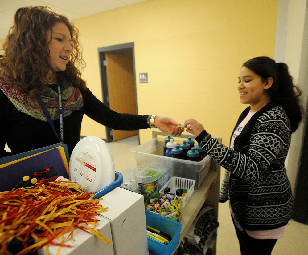"""Parker Middle School guidance counselor Meghan O'Brien, left, gives student Joceila Andrade a thumb drive in a store at the school where students """"spend"""" the red tickets that they earn for good classroom behavior."""