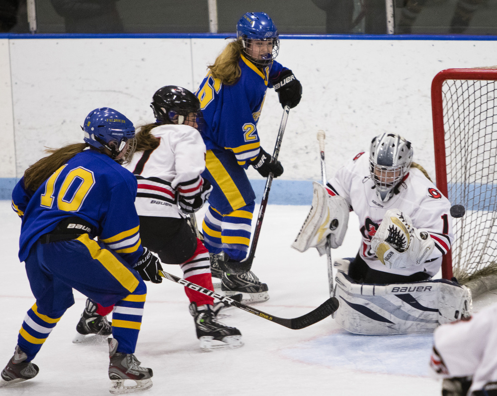 Scarborough goalie McKenzie Cormier makes a save on a shot by Falmouth's Sarah Hutcheon, center. Cormier finished with 18 saves as Scarborough improved to 14-0-1.
