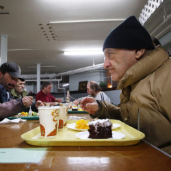 "Roland Hamel, 71, right, gets ready to dig into his Calvary City Mission meal at Calvary United Methodist Church in Lewiston on Jan. 6. ""They call me the buffet man,"" said Hamel, who is one of 50 or more people who typically receive free meals at the church."