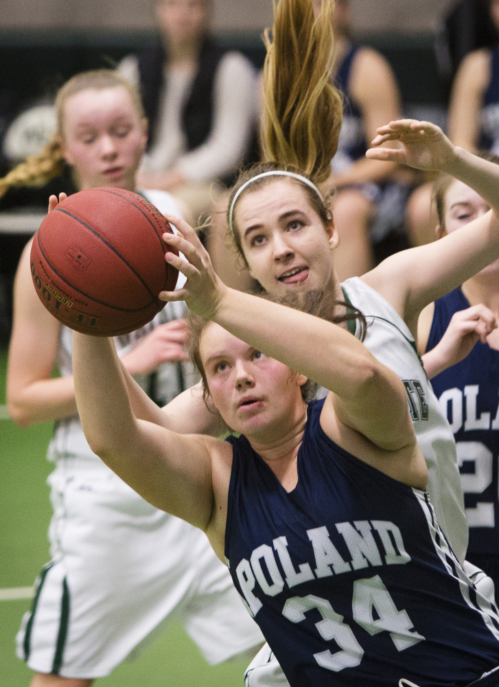Morgan Brousseau of Poland tries to grab a rebound in front of Waynflete's Annika Brooks. Brousseau finished with 11 points and six rebounds.