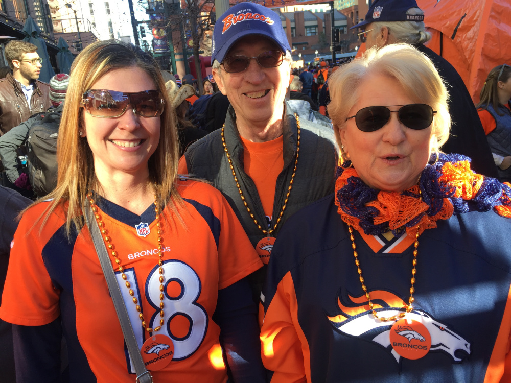 "From left, Kenya Sande, a season ticket holder from Denver, is joined by fellow Broncos fans Ron Privratsky and Kay Privratsky at a downtown rally Friday. Sande was predicting a victory for the home team, saying: ""When we're underdogs, we always win."""