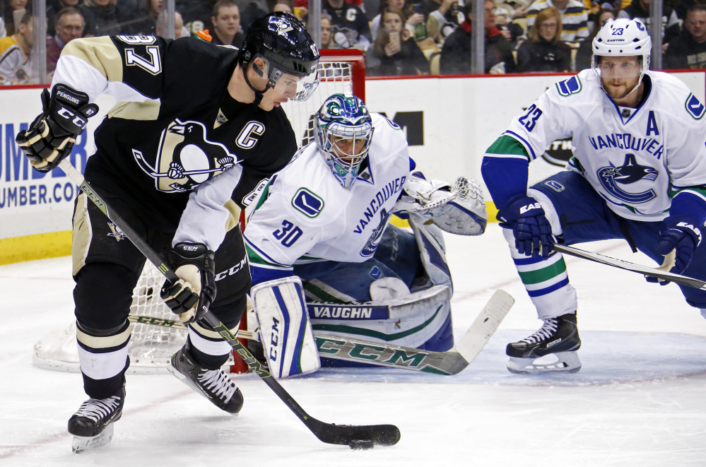 Vancouver goalie Ryan Miller and defenseman Alexander Edler try to cut off Sidney Crosby's options during Saturday's game against the Penguins. Pittsburgh won, 5-4.