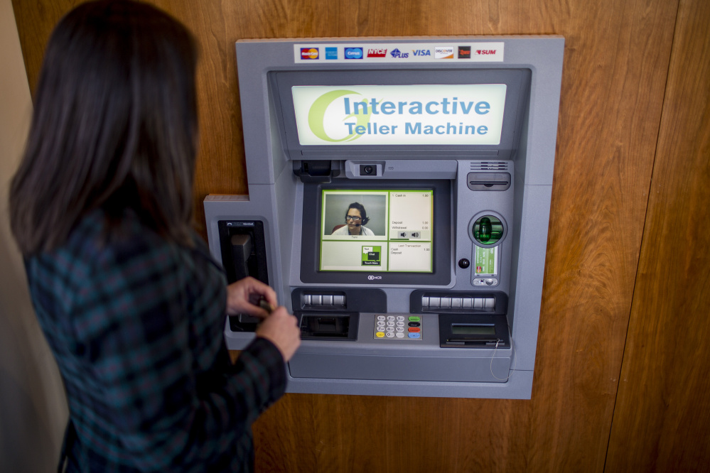 Becky Winslow, director of retail delivery for Gorham Savings Bank, demonstrates making a deposit using the bank's new Interactive Teller Machine on Munjoy Hill. A video feed of Toni, an interactive teller based in Gorham, pops up on the screen and guides Winslow through the deposit. (Photo by Gabe Souza/Staff Photographer)