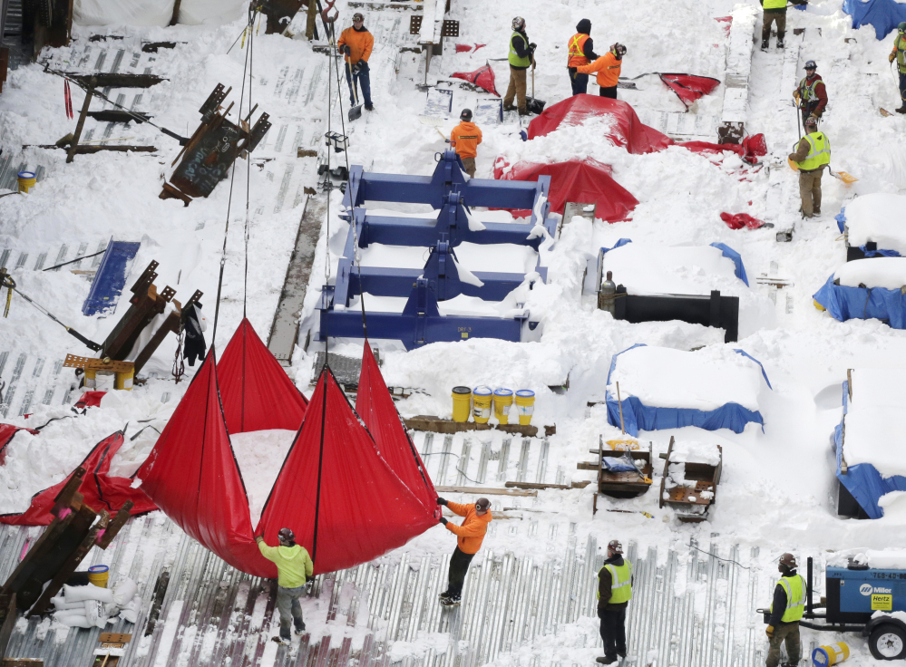 A crane hoists a large red tarp filled with snow Monday from a construction site at Hudson Yards in New York City. City officials sent out 4,600 workers and more than 2,000 pieces of equipment to clear the 27 inches of snow that fell during a blizzard Friday and Saturday.