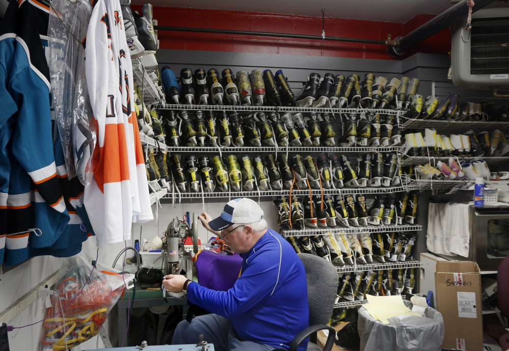 Bob Schank repairs elbow pads at Hockey Bob's Pro Shop at the Biddeford Ice Arena . Derek Davis/Staff Photographer