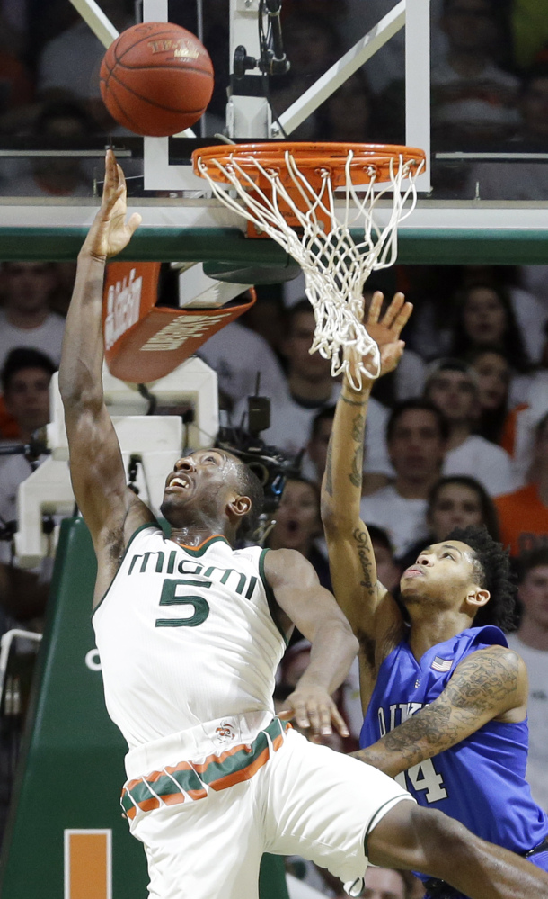Miami's Davon Reed, left, scoops a shot past Duke's Brandon Ingram during the Hurricanes' win Monday in Coral Gables, Florida.