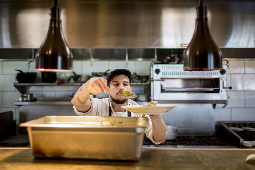 Adam Heath, kitchen manager and grill cook at Tiqa, helps himself to a serving of pesto chicken penne.