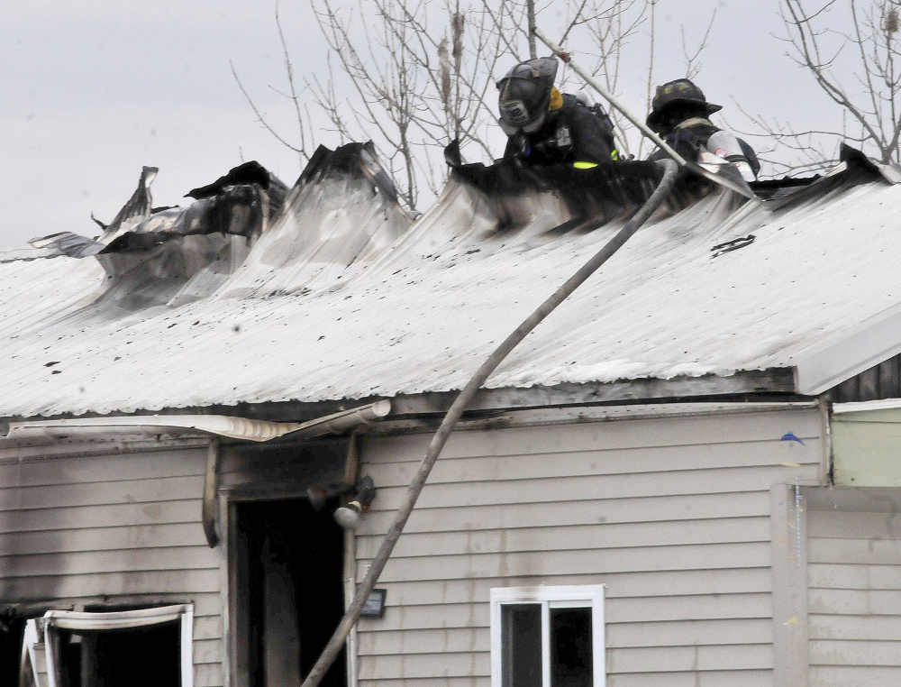Firefighters working to extinguish a fire rip a hole in the roof of a mobile home in Athens on Tuesday.