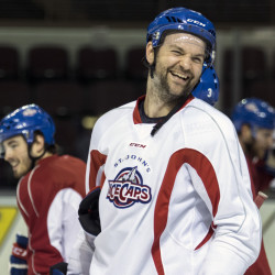 John Scott laughs with his AHL teammates as the St. John's IceCaps practice Tuesday in Portland. A social media prank led to his election as a team captain at the NHL All-Star Game this weekend.