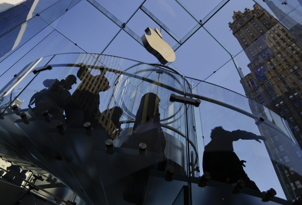 In this Sept. 19, 2014, file photo, a group of visitors to the Apple store descends a staircase to the showroom below in New York.