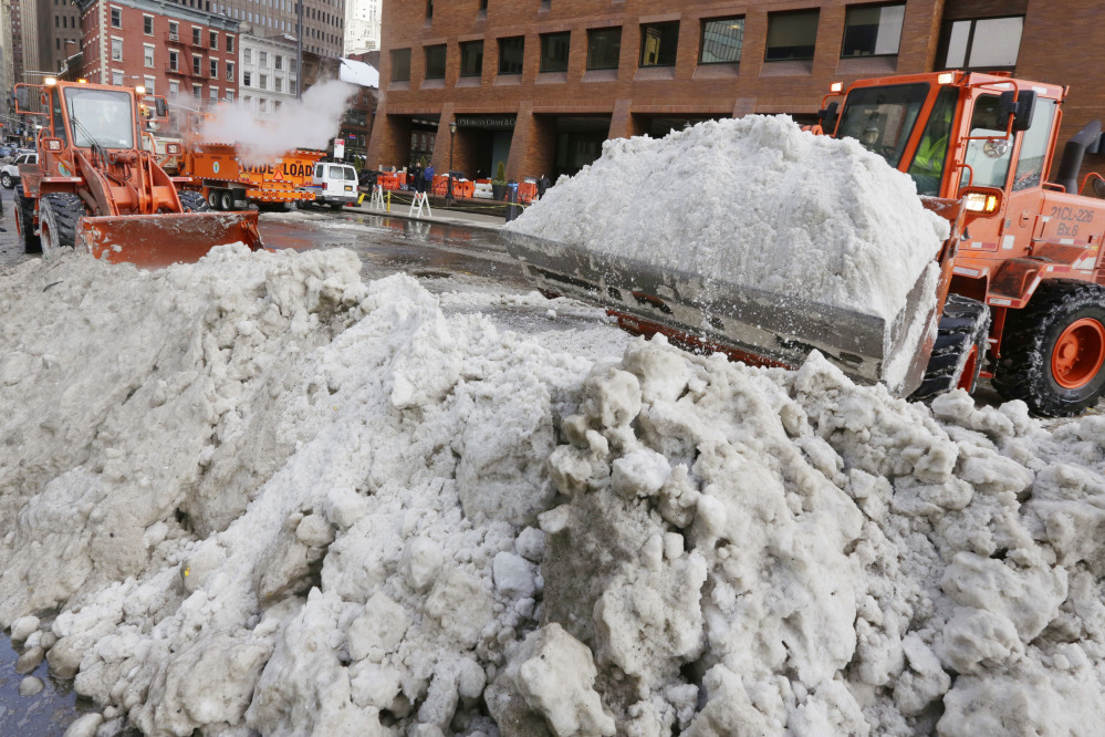 A pair of New York City Department of Sanitation front-end loaders prepare plowed snow for a melter, background left, in lower Manhattan in New York on Tuesday.
