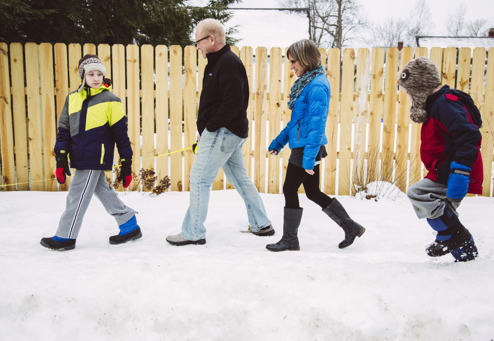 Aidan Wood, 11, his parents, David Wood and Heather Moore Wood, and his brother Ellis, 7, walki in Portland on Wednesday. When the Woods bought their house, they specifically sought a walkable neighborhood.