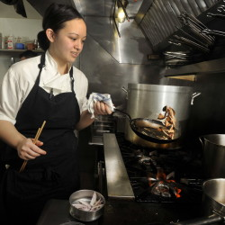 Chef Cara Stadler sautes mushrooms and shallots while preparing a dish in March 2014. Condé Nast Traveler has named her one of 10 young chefs to watch.