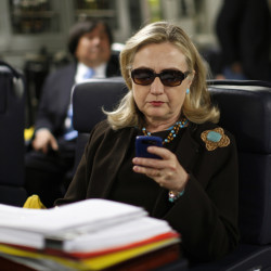Then-Secretary of State Hillary Rodham Clinton checks her Blackberry from a desk inside a C-17 military plane. The Obama administration said Friday for the first time that Clinton's unsecured home server contained some closely guarded secrets.